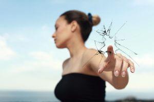 指先でガラスを割る黒いドレスの女性