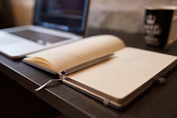 ノートパソコンと開かれたノートと紙コップ