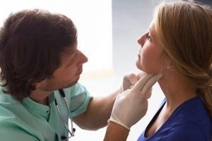 医者風の男性に検診を受ける女性