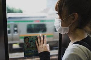 電車の車窓から電車を見るマスクの女性を後ろから撮影