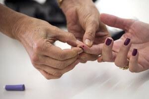 血糖測定の為に、女性の人差し指から出血。
