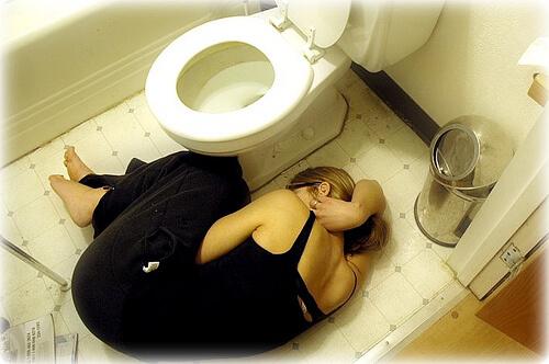 トイレの床で横たわる黒いドレスの女性