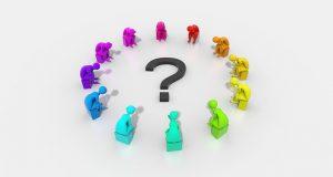 ?の周囲で円陣を組んで並ぶ7色(赤、橙、黄、緑、水色、青、紫)の人形