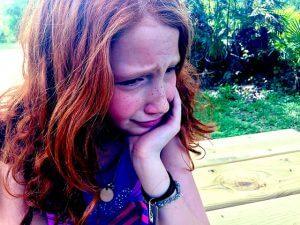 左手でほおづえをつき苦悩な表情を浮かべる赤毛の女性