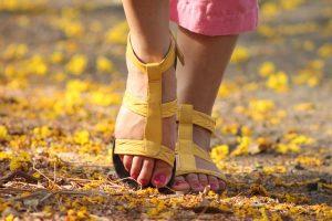 銀杏の葉が積もる地面を茶色のサンダルを履いた足が一歩踏み出そうとしている