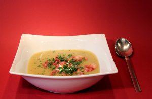 赤のテーブルに白いさらに入ったスープと銀のスプーン