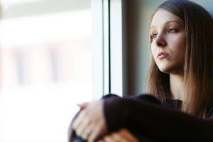 窓際で体育座りする虚ろな女性