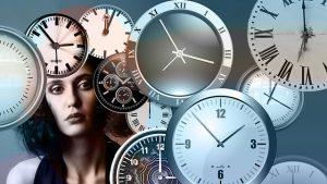女性の周りに様々な文字盤の丸時計が複数ある