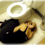 便器の横で横たわる女性