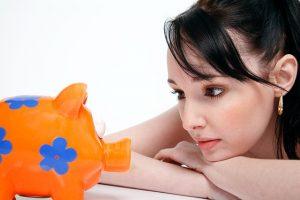 オレンジ色のブタの貯金箱を眺める女性