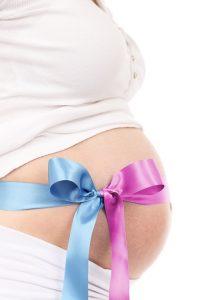 妊婦のお腹に青とピンクのリボンを蝶々結び