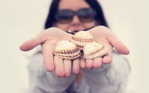 両手に3つの貝を見せてくれるサングラスの女性