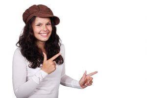 両手の指で銃の形で左を指す茶色の帽子をかぶるソバージュの笑顔の女性