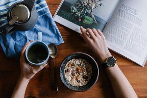 食事と雑誌とポットが置かれたテーブルを主観で見る