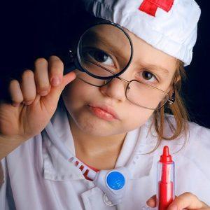 お医者さんごっこの格好で虫眼鏡を覗き込む少女