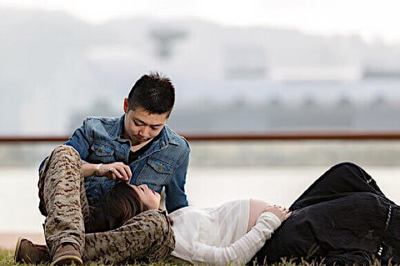 男性の膝枕で仰向けに休む妊婦