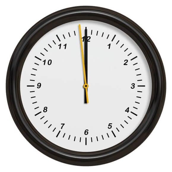 黒縁の丸型の壁掛け時計。23時59分を指す
