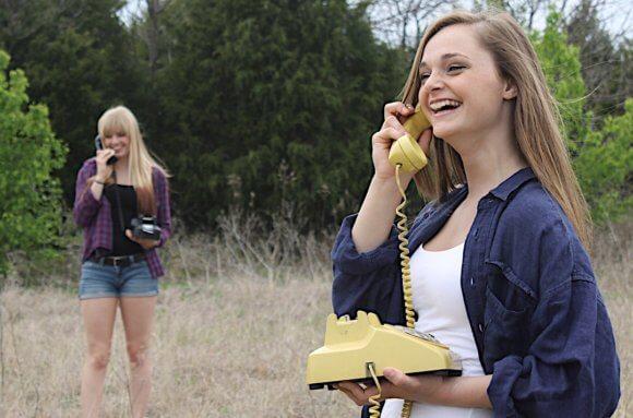 黒と黄色の固定電話を野原で持ち話す女性2人
