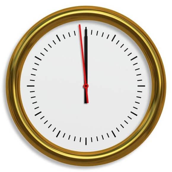 金色の縁の丸時計11時59分を指す