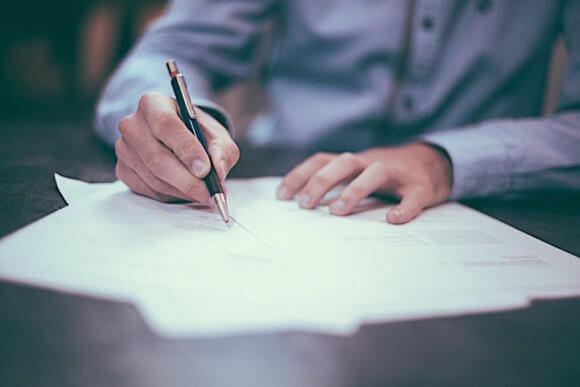 紙に何かを書く男性