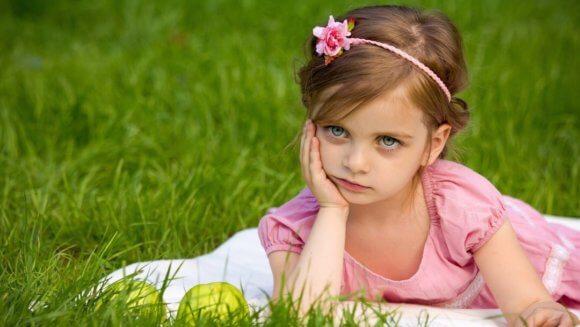 ピンクのドレスを着た可愛い少女が草原で肘をつき不機嫌な様子