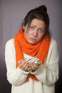 白のセーターにオレンジのマフラーをした顔色の悪い女性が薬を持っている