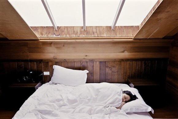 天窓の下のベッド。白いシーツに包まり、横たわる女性