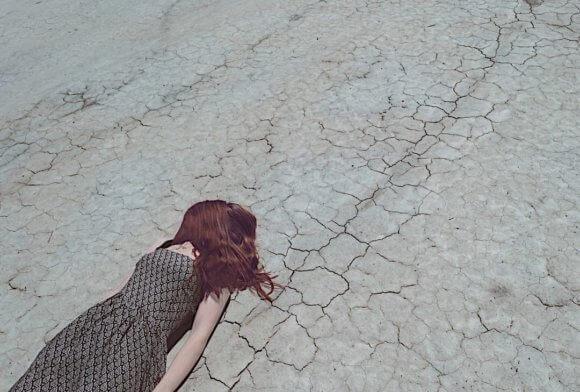 道路に仰向けで横たわるワンピースの女性。顔は自分の神に覆われて見えない