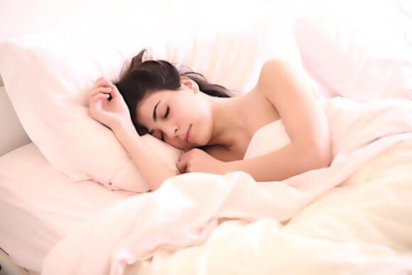 布団で入眠する女性
