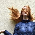 青い服を着た金髪の女性の髪が舞う