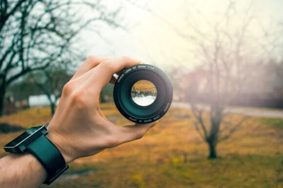 カメラのレンズを手に持ち森を見る