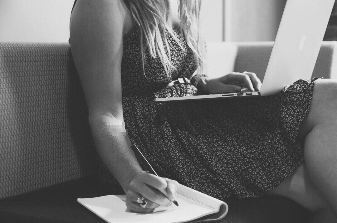 椅子に座りパソコン片手にメモを取る女性