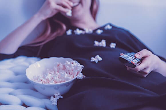 横になってテレビを見ながらポップコーンを食べ散らかす、紺色の服の女性