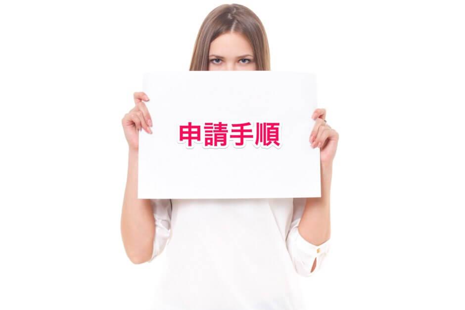 申請手順という紙を持つ女性