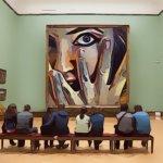 顔を覆う女性の絵画を眺める男女