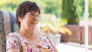 椅子に座り微笑む眼鏡をかけた年配の女性