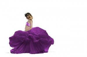 紫のスカートがたなびく。横向きでお腹に手を当てる水着の女性