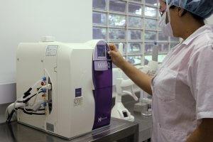 何かの機械を触っている白衣の女性