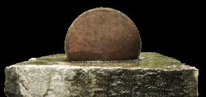 四角の石の台座に丸い石が乗り水が張っている