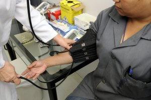 白衣を着た人が女性の血圧を測る